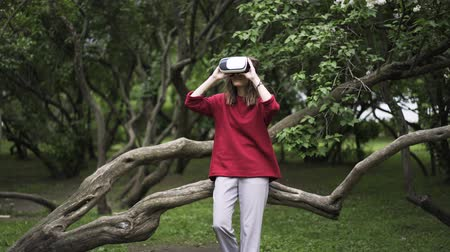 experiência : Young woman wearing a red sweater is using VR glasses while being at a park near large tree. Locked down real time establishing shot Stock Footage