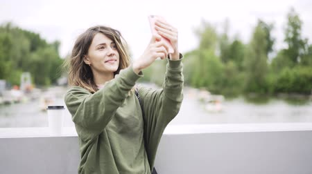 camera move : Happy young woman wearing a green sweatshirt is standing on a bridge and taking a selfie. She is using her smartphone and having a good time. Left to right pan real time establishing shot