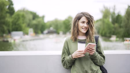 mobile music : Young woman wearing green casual clothes is listening to the music with her smartphone and headphones and drinking coffee. Locked down real time establishing shot