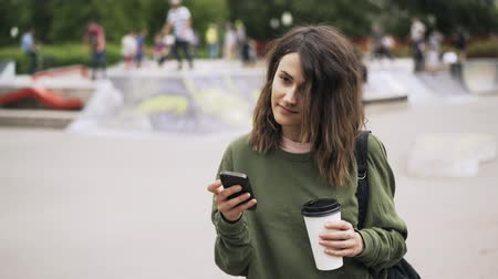 texto : Young woman wearing a green sweatshirt is holding a large cup of coffee and texting. Blurred skateboarders are in the background. Locked down real time establishing shot