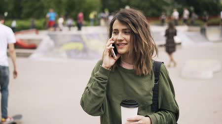 trancado : Young woman wearing a green sweatshirt is holding a large cup of coffee and talking on her smartphone. Blurred skateboarders are in the background. Locked down real time establishing shot