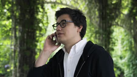 arbusti : Pretty young man wearing glasses is enjoying a stroll in a park and a phone conversation and smiling. Handheld real time close up shot
