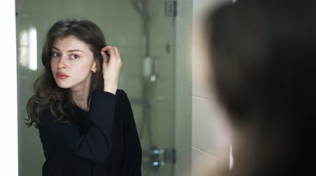 туалетные принадлежности : Pensive young woman wearing black clothes is looking at her reflection in a mirror and combing her hair with a hand. Handheld real time close up shot