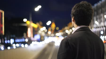 országúti : Rear view of an unrecognizable young businessman looking at cars passing by while standing on a bridge at night. Handheld real time medium shot