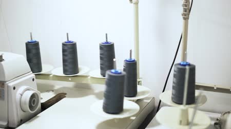 hímzés : Working process of an industrial sewing machine with six gray spools of thread. Handheld real time close up shot