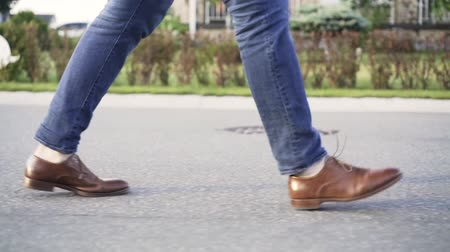 cadarço : Unrecognizable man wearing blue jeans and brown leather shoes is walking in the street with no traffic. Side view. Tracking real time establishing shot
