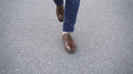 cadarço : Unrecognizable man wearing blue jeans and brown leather shoes is walking in the street with no traffic. Top view. Tracking real time establishing shot Vídeos