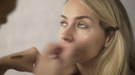 rímel : Beautiful blonde model is having her makeup applied to her eyes with a brush. Concept of beauty and a fashion industry. Handheld real time establishing shot