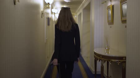 lobby : Rear view of a young businesswoman wearing a dark suit walking in a hotel lobby and opening a glass door. Tracking real time establishing shot