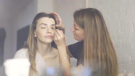 close up shot : Beautiful model with freckles is sitting in a studio while a makeup artist with long hair is applying a toning cream to her eyelids. Locked down real time establishing shot