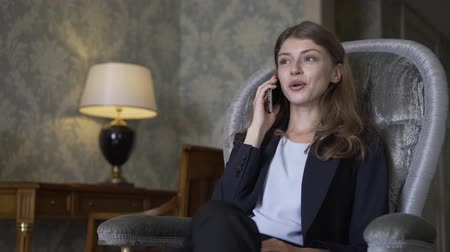 desgaste formal : Attractive young woman wearing a suit is sitting in an armchair in a luxury hotel room, smiling and talking on her smartphone. Handheld real time medium shot