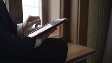 first person : Unrecognizable young businessman is sitting on a windowsill and using his tablet computer. Locked down real time establishing shot