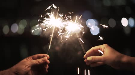 kutluyor : Hands of an unrecognizable man and woman holding sparklers. A blurred night background. Handheld real time establishing shot Stok Video