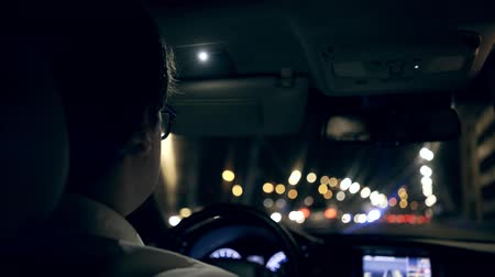 hátsó megvilágítású : Rear view of an unrecognizable young businessman wearing a white shirt and glasses driving his car through a night tunnel. Handheld real time establishing shot