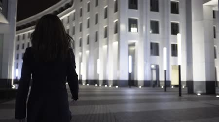 hátsó megvilágítású : Rear view of a young businesswoman wearing a black suit and walking in a night city. Tracking real time establishing shot Stock mozgókép