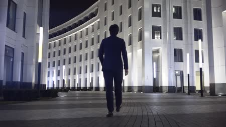 desgaste formal : Rear view of a young businessman wearing a black suit and walking in a night city. Concept of success. Tracking real time establishing shot