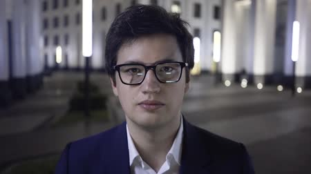 dobranoc : Attractive young businessman wearing a dark suit and glasses is looking to the camera with a grave expression. Then he is smiling. Concept of business and madness. Handheld real time establishing shot