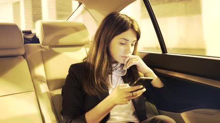 cabins : Serious young businesswoman with dark hair is looking at her smartphone screen while riding in a car and thinking. Handheld real time medium shot Stock Footage