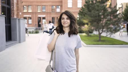 attorney : Cheerful young woman with dark hair wearing a gray T shirt is walking from a clothes store with paper bags and waving to a friend off screen. Tracking real time medium shot Stock Footage
