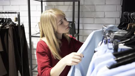 perchas de ropa : Blonde woman wearing a red sweater is choosing clothes for office in a store. Handheld real time medium shot Archivo de Video