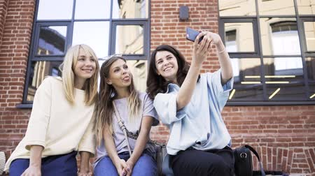 carelessness : Three young women are sticking out their tongues and taking a selfie while being in the summer street. Handheld real time medium shot Stock Footage