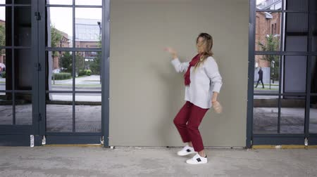 Attractive young woman wearing a white sweater and red pants is dancing in the street on a cloudy day. Locked down real time medium shot 動画素材