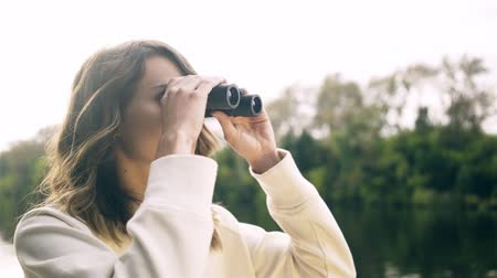 Beautiful young woman in a white cardigan is using a pair of binoculars while riding on a boat in a river. Handheld real time medium shot