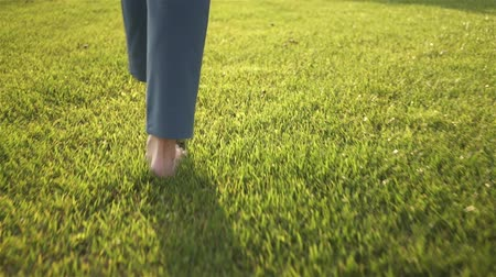 Rea view of an unrecognizable young woman walking on the grass barefoot. Concept of freedom and enjoying one s life. Tracking real time medium shot