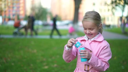 sabão : Cute little blonde girl wearing a pink coat is playing with soap bubbles in an autumn park. Handheld real time medium shot