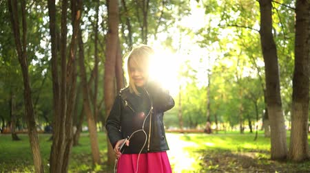 Cute little girl wearing a leather jacket listening to the music and dancing in a park on a summer day. Handheld real time medium shot