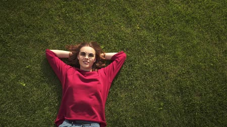 Top view of a cheerful young girl wearing sunglasses and a red sweater and lying on the grass with her hands behind her head. Handheld real time medium shot 動画素材