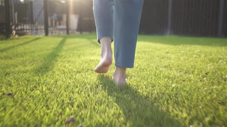 walk behind : Unrecognizable young woman walking on the grass barefoot. Concept of freedom and enjoying one s life. Tracking real time medium shot