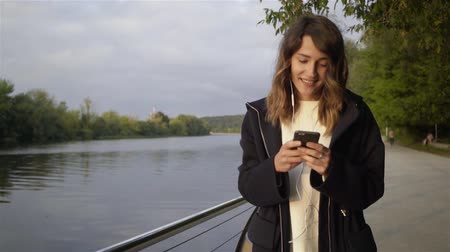 Calm young woman wearing a black hoodie listening to the music and walking along a river bank. Tracking real time establishing shot 動画素材