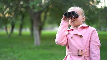 Cute little girl wearing a pink coat is using binoculars to look at something in a distance. Handheld real time establishing shot