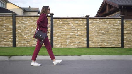 Side view of a businesswoman wearing glasses and a red suit texting on her way to work on a summer day. Suburbs Tracking real time medium shot