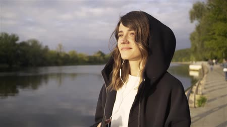 Calm young woman wearing a black hoodie listening to the music and dancing on a river bank. Right to left pan slow motion establishing shot