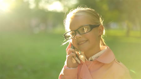 Cute little girl in glasses standing and talking on her smartphone while being in a park. Handheld slow motion establishing shot