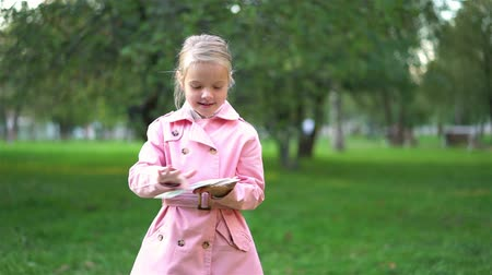 Cute little blonde girl wearing a pink coat throwing away a pack of dollar bills while standing in a park. Handheld slow motion medium shot