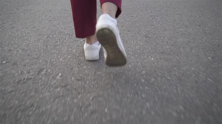 Rear view of legs of a young woman wearing dark red trousers and white shoes walking on a sidewalk. Tracking slow motion close up shot