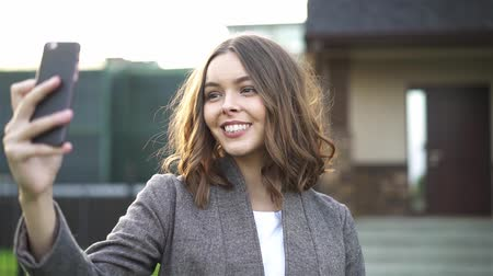 Beautiful young woman with dark hair wearing a suit is taking a selfie in a suburb street. Handheld slow motion establishing shot