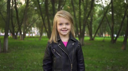 Happy little blonde girl wearing a leather jacket is smiling and air kissing in a park on a summer day. Handheld slow motion medium shot