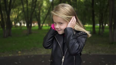 Cute little blonde girl not listening and closing her ears with palms in a park on a cloudy summer day. Handheld slow motion medium shot