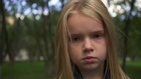 Serious little girl with light hair looking at camera while standing in a park on a cloudy summer day. Handheld slow motion close up shot Stock Footage