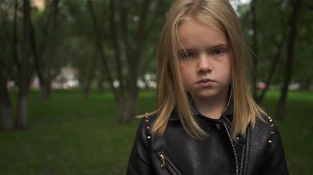 Serious little girl with light hair wearing a jacket looking at camera while standing in a park on a cloudy summer day. Handheld slow motion close up shot Stock Footage
