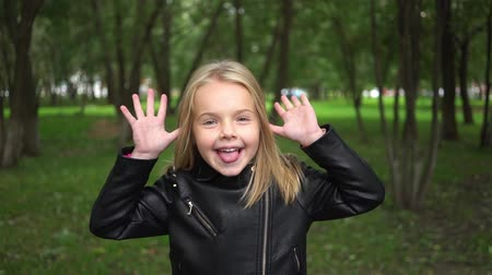 Cute little blonde girl making funny faces in a park on a cloudy summer day. Handheld slow motion medium shot Stock Footage
