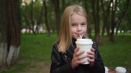 Cute little blonde girl drinking soda in a park on a cloudy summer day. Handheld slow motion medium shot Stock Footage