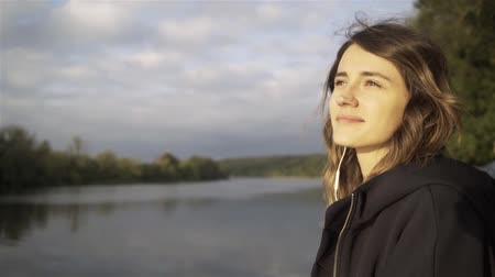 Cheerful young woman wearing a black hoodie listening to the music and standing on a river bank. Tracking real time establishing shot Stock Footage