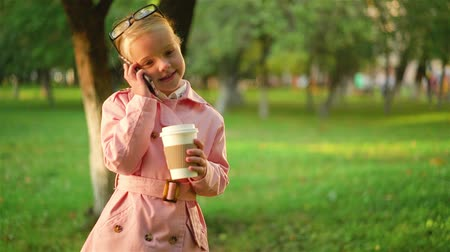 Little girl in a pink coat talking on her smartphone and holding a cup of coffee while standing in a park. Left to right pan real time establishing shot