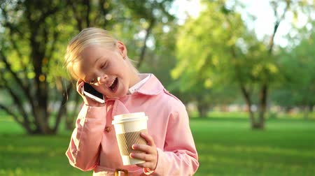 Little girl in a pink coat talking on her smartphone and holding a cup of coffee while walkin in a park on a sunny day. Tracking time establishing shot