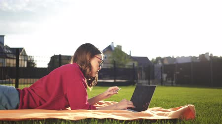 Teen girl in glasses and a red sweatshirt lying in her backyard with a laptop on a summer day. She is entering her credit card number to buy on line. Locked down real time medium shot Stock Footage